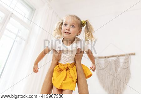 Dad Playing With His Baby Daughter, He Holds Her In His Arms. Selective Focus On Baby's Face