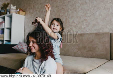 A Little Girl Does Her Mothers Hair While Playing Together. Childrens Entertainment For Mothers And