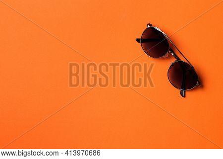 Male Sun Glasses On Orange Paper Background. Men Eyewear Fashion Concept. Minimal Style, Flat Lay.