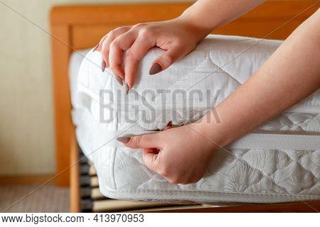 Female Hands Put New Mattress Pad On Orthopedic Mattress Corner. Bed Linen At Home. Sheet Is Worn On