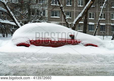 Red Car Stands In A Deep Snowdrift After A Hard Snowstorm In Winter