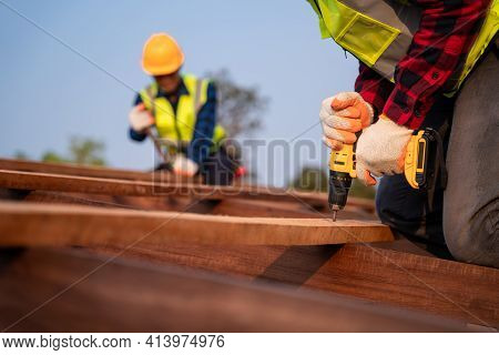 Close Up Roofer Working On Roof Structure Of Building On Construction Site, Roofer Using Air Or Pneu