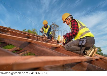 Two Construction Worker Install New Roof, Roofing Tools, Electric Drill Used On New Roofs Of Wooden