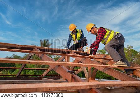 Asian Construction Worker Install New Roof, Roofing Tools, Electric Drill Used On New Roofs Of Woode