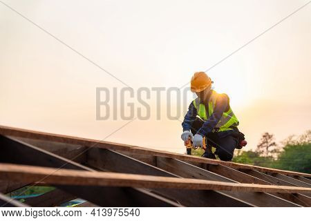 Asian Roofer Working On Roof Structure Of Building On Construction Site, Roofer Using Air Or Pneumat