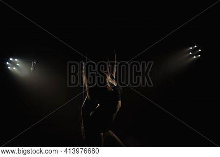 Beautiful Slim Girl With Pylon. Female Pole Dancer Woman Dancing On A Pole On A Black Background.
