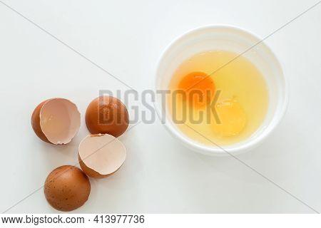 Raw Broken Chicken Eggs And Broken Shells. Egg Yolks In A White Plate