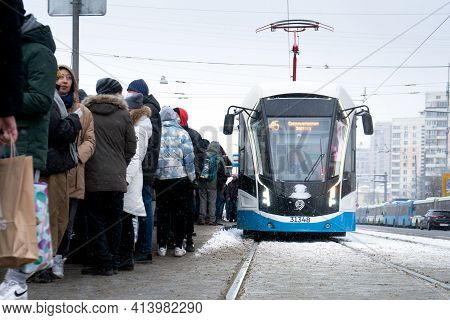 Moscow, Russia - January 31, 2021:crowd Of People On The Tram Stop And A Moscow Tram On The Stop Dur