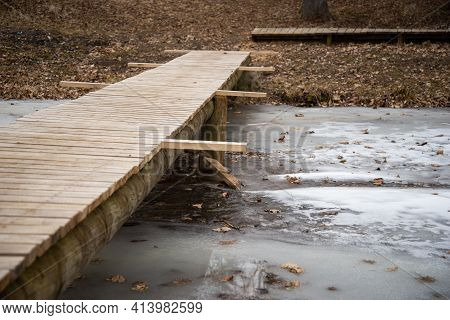 Wooden Pedestrian Bridge Made Of Wooden Planks Over A Frozen River In Early Spring. The Bridge Is St