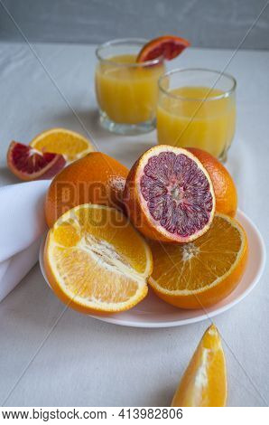 Sweet And Juicy Blood Oranges And Oranges, Whole And Cut On A White Plate And Gkasses Of Fresh Orang