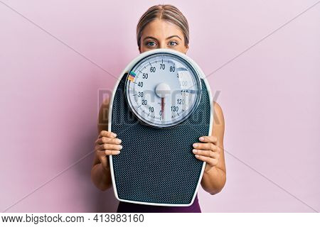 Beautiful blonde woman holding weight machine to balance weight loss smiling with a happy and cool smile on face. showing teeth.