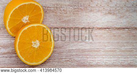 Oranges On The Table. Orange Halves On A Wooden Background.