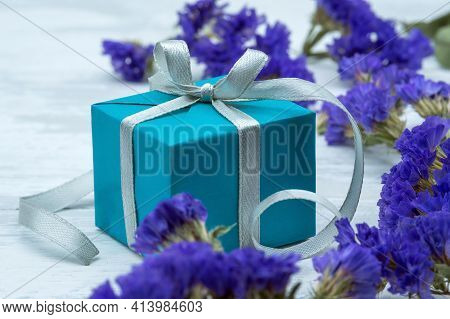 Gift Wrap And Blue Flowers. A Blue Box With A Gray Ribbon. Blue Gift Box On Wooden Background.