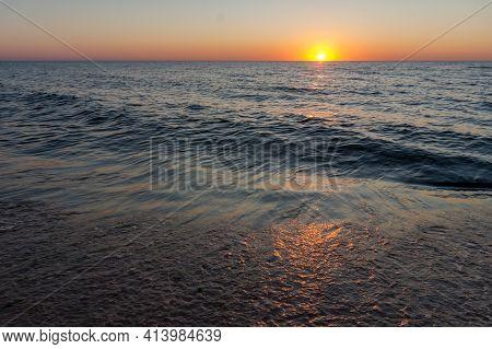 Sunset On The Seashore. The Sun Is Setting Behind The Sea Horizon.