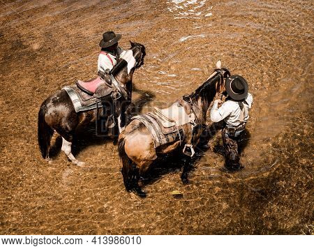 Old And Young Cowboys Rest With Their Horses In The Stream After They Finish Bathing