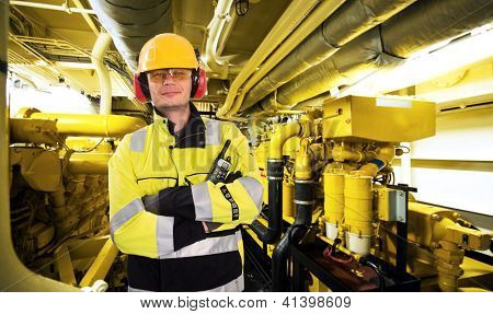 Proud mechanic, posing with his arms crossed, a hard hat, goggles, gloves and a reflective coat in the engine room of an industrial offshore supply ship