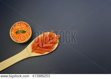 Red Penne Pasta In A Wooden Spoon And Red Lentils In A Round Bowl On A Gray Background. Red Lentil P