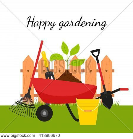 A Garden Wheelbarrow With A Plant And Tools On The Background Of A Fence And Grass. The Concept Of G