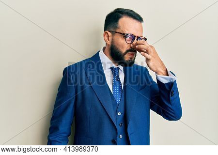 Young man with beard wearing business suit and tie smelling something stinky and disgusting, intolerable smell, holding breath with fingers on nose. bad smell
