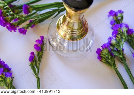Still Life With Perfume Bottle On White Wooden Background Across Purple Statice Flowers. Top View. C