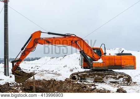 A Large Orange Excavator Digs A Hole At A Construction Site In The Winter. Orange Mechanical Digger