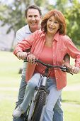 Couples sat on a bike smiling poster