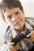 Boy plying on games console at home poster