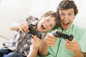 Man and son plying on games console at home poster