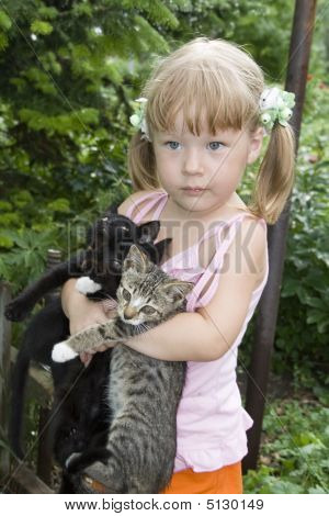 Small girl embraces by hands three kittens poster