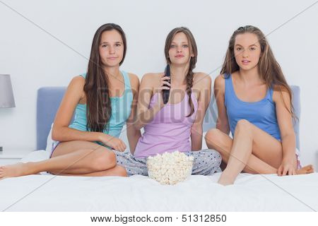 Girls sitting on bed at sleepover with popcorn and looking at camera