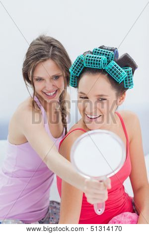 Girls sitting in bed looking in mirror with one girl wearing hair rollers at sleepover