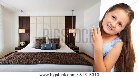 Little girl holding picture of modern bedroom