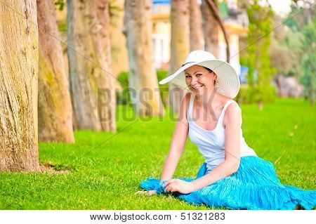 Girl Resting On The Lawn And Laughs Gaily