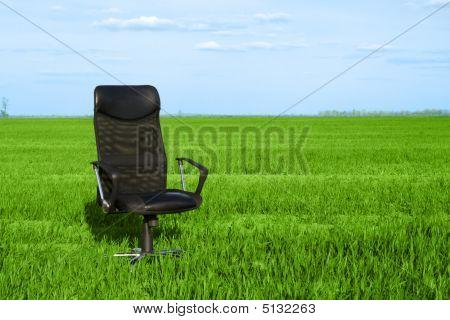 Bürostuhl im grünen Gras mit einem tiefblauen Himmel