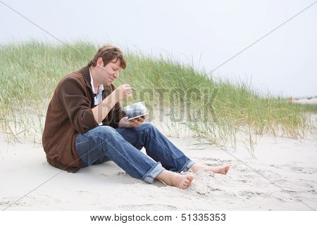 Young Happy Man Relaxing On Sand Dunes Of The Beach Of St.peter Ording
