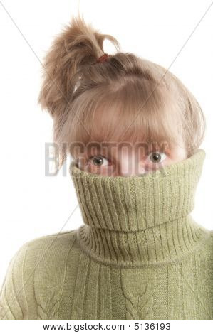 Young Woman Hinding Face Behind Collar Of Her Sweater