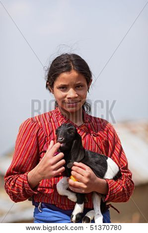 NAGARKOT, NEPAL - APRIL 5: Portrait of young unidentified Nepalese girl with a kid goat on April 5, 2009 in Nagarkot Village, Kathmandu, Central Region, Nepal.