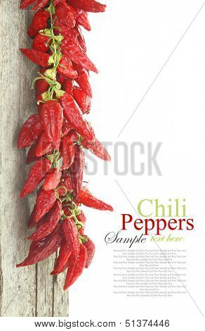 Red hot chili peppers hanging on wood, isolated on white
