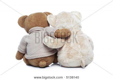 Vista posterior de dos osos de peluche, abrazándose unos a otros sobre blanco