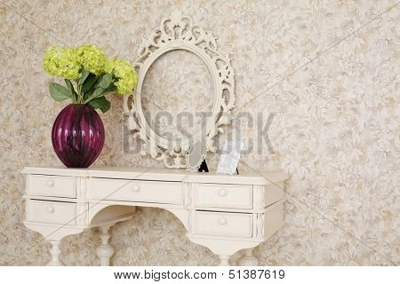 Wooden carved dressing table with blank frame and flowers in light room.