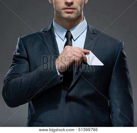 Part of body of man who takes out white card from the pocket of business suit, copyspace