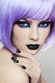 Close-up portrait of young beautiful woman with colorful fancy make-up and violet wig poster
