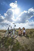 Two pretty girls on bike tour on rock path poster