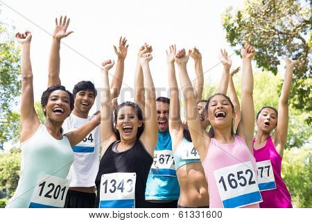Group of marathon runners cheering after winning a race in the park