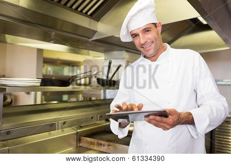 Portrait of a smiling male cook using digital tablet in the kitchen poster