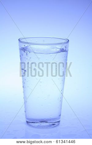glass of clear liquid with blue tone