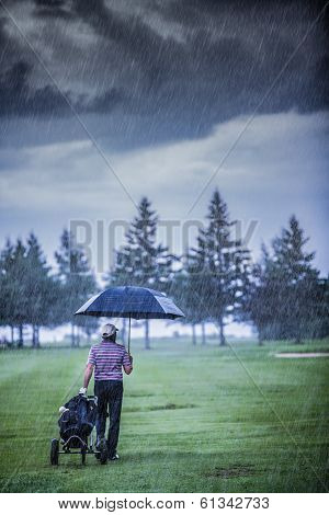 Golfer On A Rainy Day Leaving The Golf Course