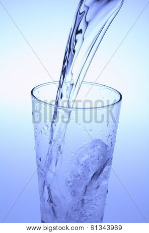 glass with clear liquid pouring