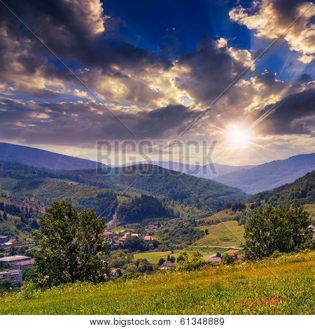 Village In Mountain Foot Valley With Forest At Sunset