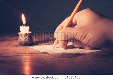 Closeup on a hand writing by candlelight poster